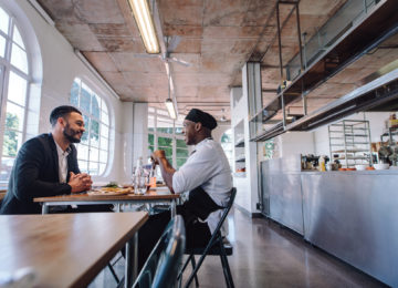 Two male business owners discuss qualified improvement property