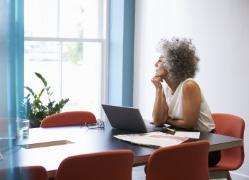 Image of woman looking of window in boardroom and reviewing NOL rules