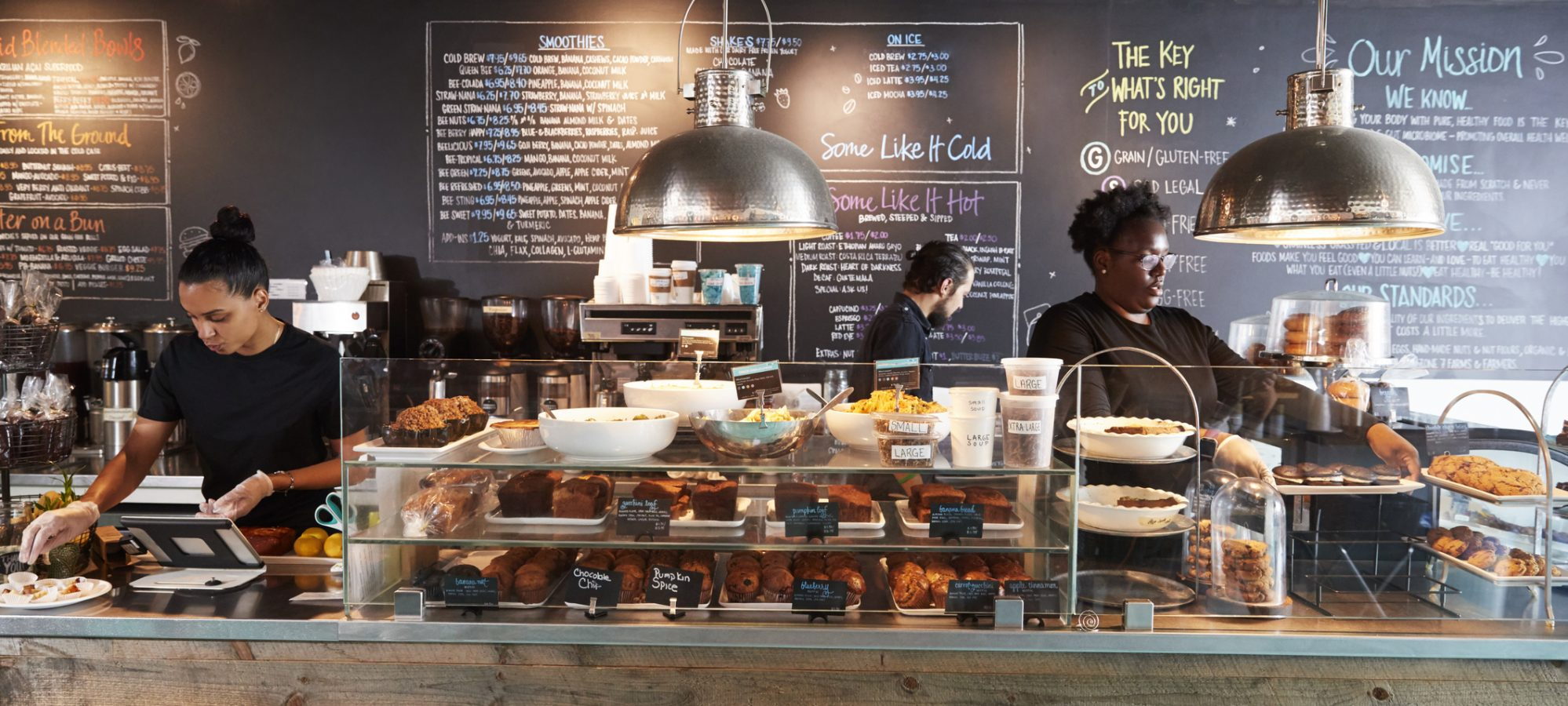Image of minimum wage staff working behind counter in coffee shop