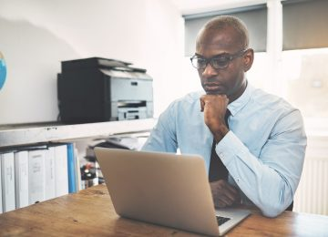 Businessman reading top 6 changes in Tax Cuts and Jobs Act on laptop