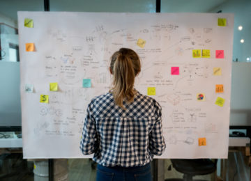 Woman sketching a nonprofit finance transformation plan on a placard at a creative office