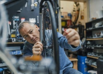 Image of business owner repairing bike in shop - eligible for QBI deduction