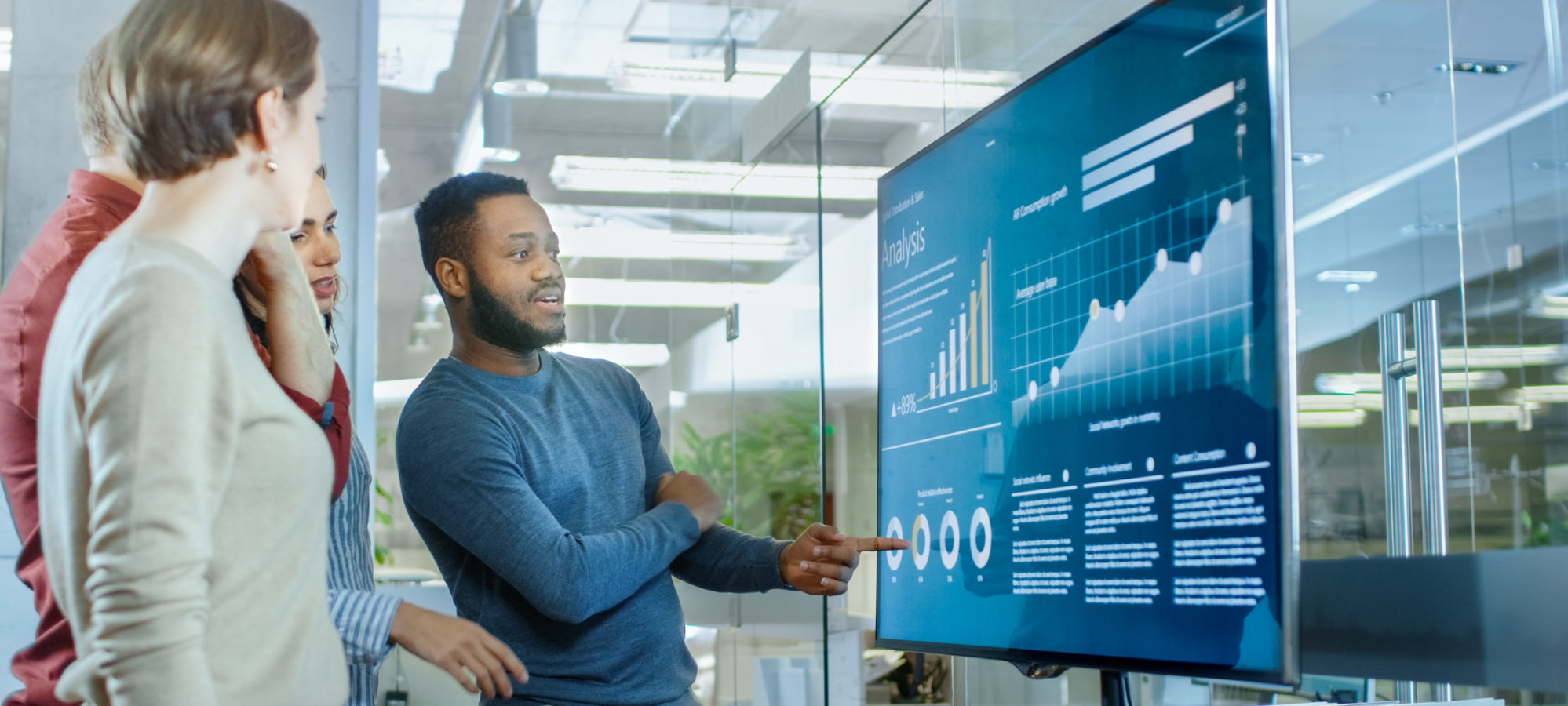 Four coworkers looking at company's real-time financial data on digital screen