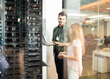 Two business people standing in server room evaluating cloud vs. on-premise solutions