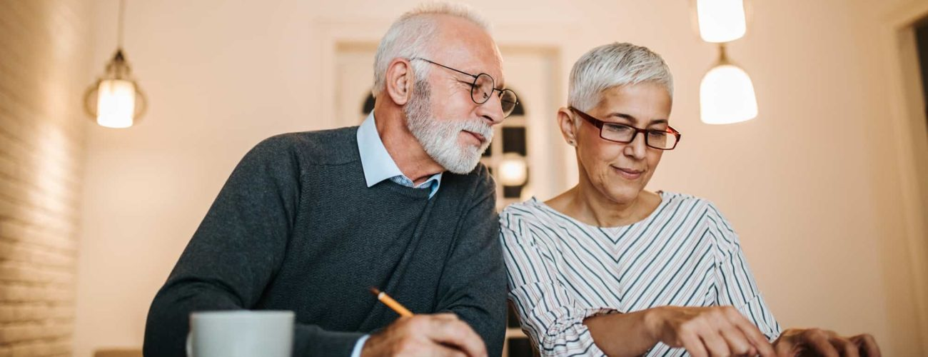 Mature couple reviewing new 2020 contribution limits for retirement